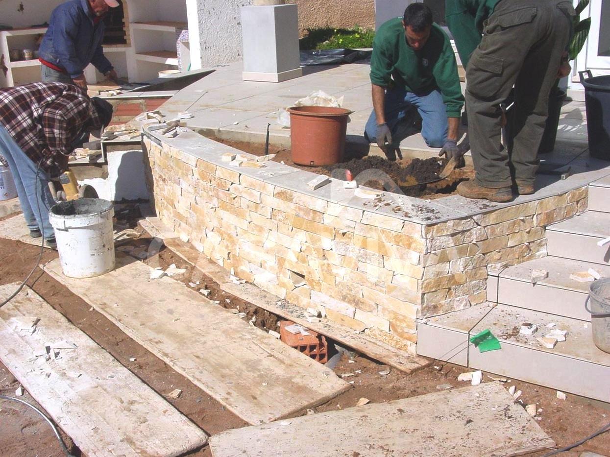 Revestimento de canteiros em pedra natural e enchimento com terra para jardim.