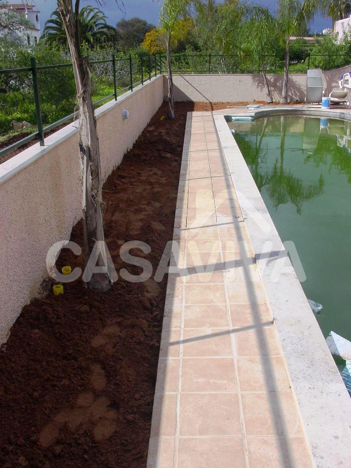 Pavimento envolvente da piscina com revestimento em mosaico e zona a ajardinar.