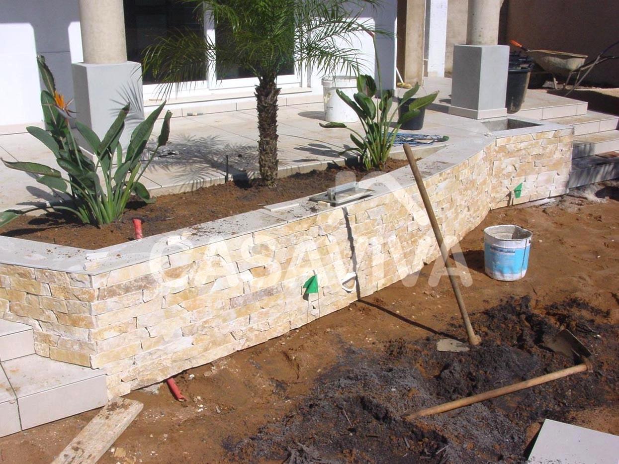 Construção de novo canteiro com paredes revestidas a pedra natural.