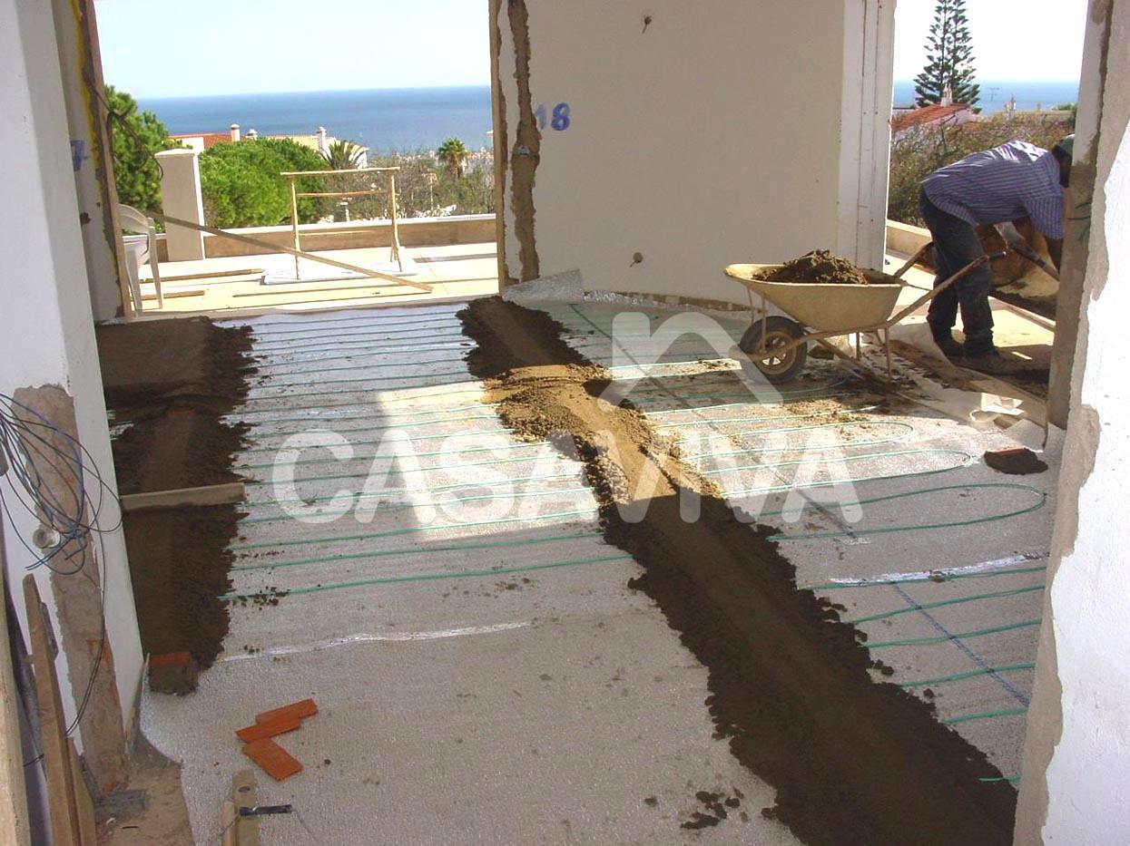 Aplicação de isolante térmico e pavimento radiante sob a betonilha de regularização em moradia.